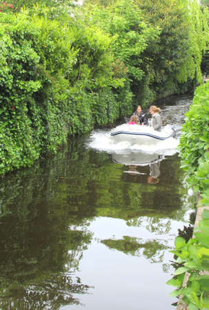 plassen: Loosdrecht, Netherlands, may 2014 Young people navigate in a motor-boat in the lakes of Loosdrecht, Holland