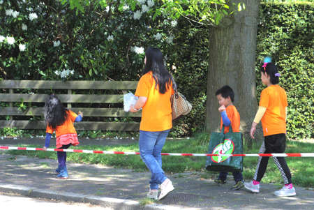 Soest, Netherlands, April 2014 Asian family in orange sweaters in Holland