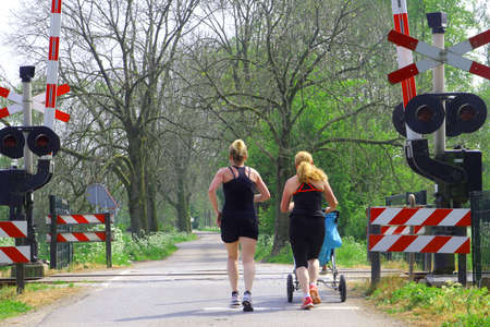 Geldermalsen, Netherlands, may 2014 Young women are jogging with a baby in the stroller to lose weight and get a better condition
