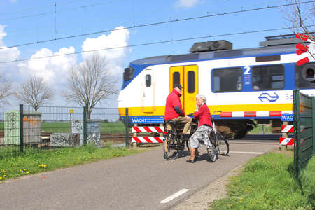 Soest, Netherlands, april 2014 Elderly couple on bikes waits for the train at a railway crossing