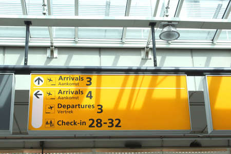 Notice board with information about arrivals and departures and check-in counters at Schiphol Amsterdam International Airport