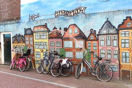 Leeuwarde, Friesland, Netherlands, may 2014 Bikes along an artistic painted wall with old canal houses