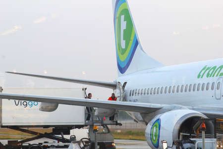 eindhoven: Eindhoven airport, Netherlands, june 2014 People are loading cargo in a Boeing 737 of Transavia Editorial