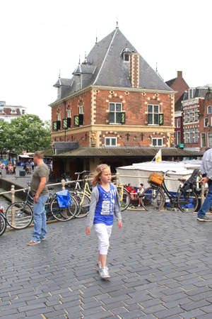 leeuwarden: Leeuwarde,Friesland,Netherlands,2014 Girl at the historic building the Weigh House in the city centre of Leeuwarden