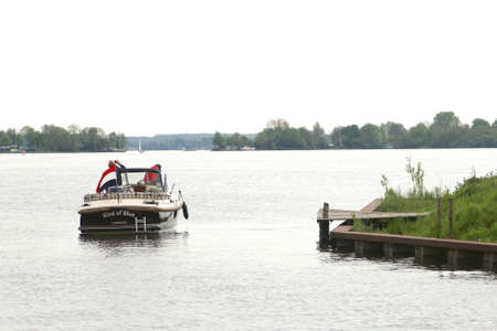 plassen: Loosdrecht, Netherlands, may 2014 People navigate in a motor-boat in the lakes of Loosdrecht, Holland