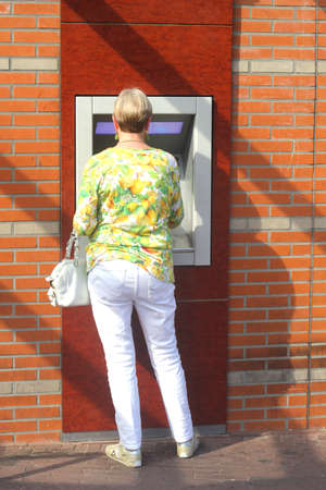 creditcards: Netherlands, may 2014 Woman gets money with a banking card from the cash machine