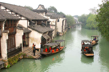 Wuzhen, Zhejiang province, China, novemer 2014 Tourist boats in a canal along the ancient houses in the famous water town of Wuzhen (Unesco World Heritage)