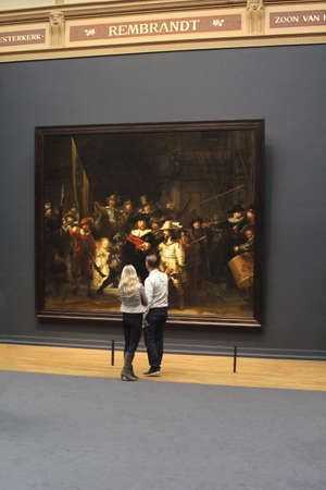 admires: Amsterdam, Netherlands, december 2014 Couple admires painting the Night Watch (Nachtwacht) of Rembrandt in the Rijksmuseum