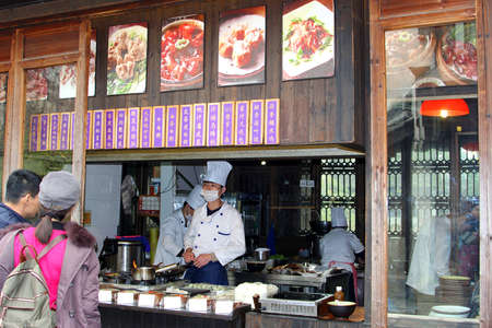 culinary tourism: Wuzhen China in November 2014 Couple is choosing a dish in a takeaway restaurant in Wuzhen