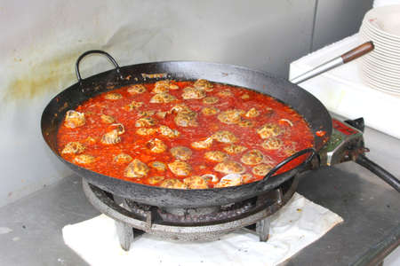 gastronome: Cooking pot with red sauce and shell-fish in China