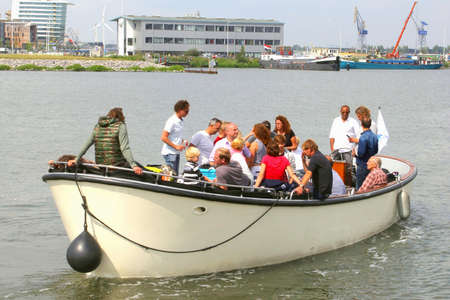 amusment: Amsterdam, Netherlands, August 19, 2015 People are sailing in a demolition and will watch the tall ships falling on the Sail 2015 event Editorial