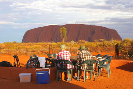 uluru: Ayers Rock, NT, Australia, march 2013, Couple enjoys the Uluru Ayers Rock during sunset with a picnic and a glass of wine Editorial
