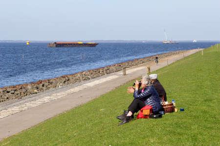 mujer mirando el horizonte: Noordoostpolder, Flevoland, Pa�ses Bajos, en abril de 2015, Pareja disfruta de la vista en el IJsselmeer lago cae en un d�a de campo