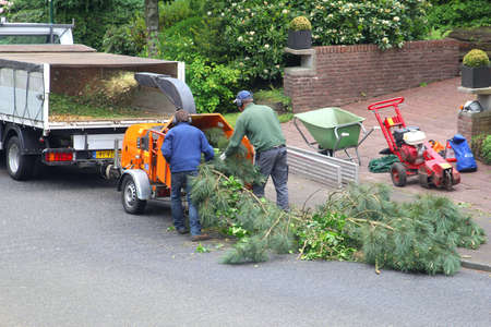 soest: Soest, Netherlands, May 2014, Gardeners are working with the wood shredder for the branches of a tree Editorial