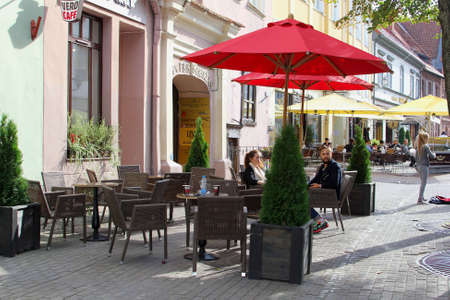 gastronome: Vilnius, Lithuania, October 2015 Young couple relax at a cafe terrace in Pilies Street in the Old twon of Vilnius