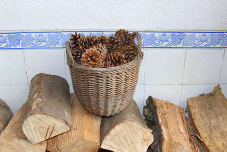 specifies: Wicker basket with dried pine cones and wood blocks for the open fireplace. On a white background with antique blue tiles