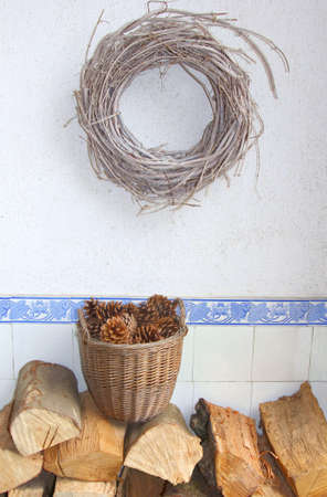 specifies: Wicker wreath, pine cones and wood blocks for the fireplace. On a white background and antique blue tiles with lotus flowers