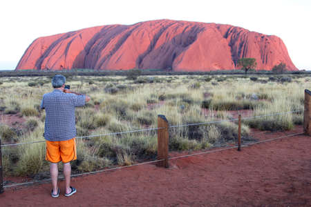 tjuta: Uluru Kata Tjuta, Northern Territory, Australia, December 2015 Tourist is photographing the purple colors of the sunset at Uluru Ayers Rock
