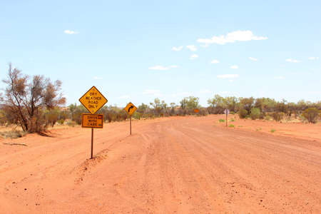 driving conditions: Warning signs for dry-weather road only, Red Centre of the Australian Outback Stock Photo