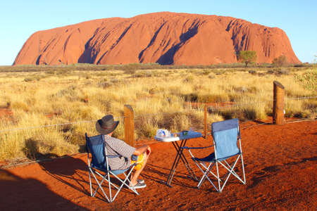 ayers: Yulara, Northern Territory, Australia, December 2015 Tourist Has A picnic and enjoys the spectacular sunset Uluru or Ayers Rock in Uluru Kata Tjuta National Park