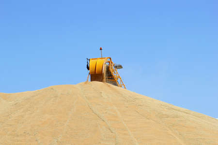 grounding: Machine is grounding harvested grain at a blue sky background Stock Photo
