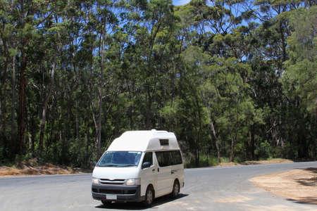 karri: Camper van drives in the Karri trees forest, Western Australia Stock Photo