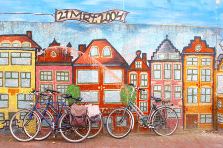 surrealist: Leeuwarden, The Netherlands, May 2014 bikes against a wall with street art canal houses in Amsterdam style Editorial