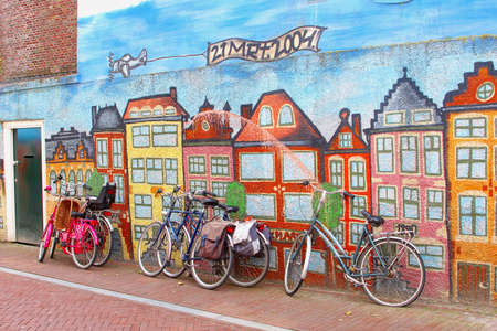 surrealist: Leeuwarden, The Netherlands, May 2014 Bicycles at a mural pating with canal houses in Amsterdam style Editorial