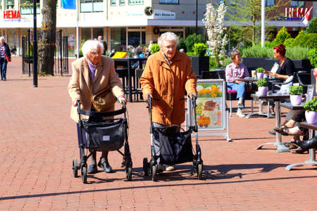 self dependent: Soest, Netherlands, April 2014 Active elderly ladies are shopping with walkers in the shopping street