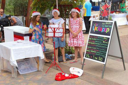 christmas carols: Alice Springs, Australia, December 2015 Girls are singing Christmas carols at the weekly outdoor market Editorial