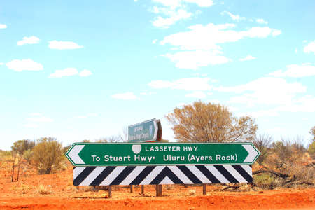 letreros: Signboards to the Stuart Highway and Uluru Ayers Rock at a crossing of the Lasseter Highway, Australia