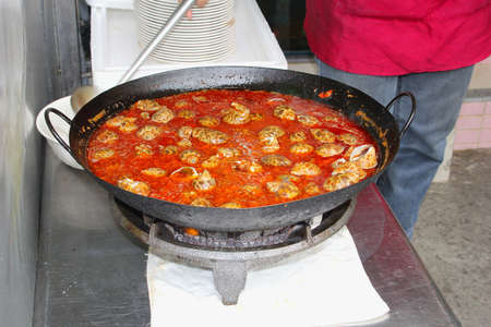 caterers: Woman prepares sea shells in a red sauce in a cooking pot