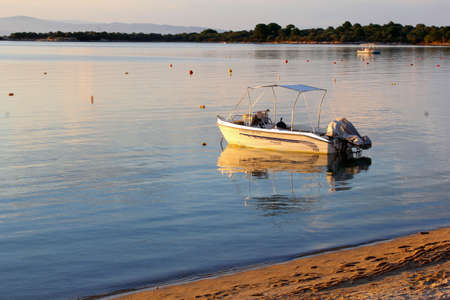 sports shell: Vourvourou, Chalkidiki, Greece, June 2016 Boat and reflections at sunset in the Aegean Sea