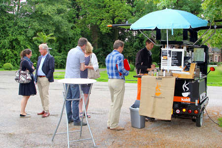 franchising: Breukelen, Netherlands, July 2016 People buy takeaway coffee at an ambulatory coffee stand in a small car