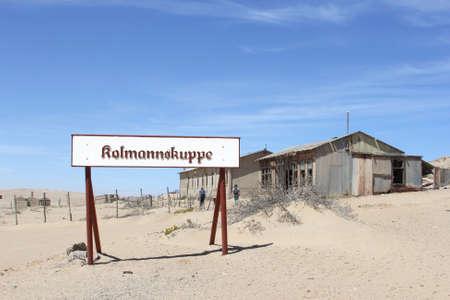 clavados: Kolmannskuppe, Namibia, de octubre de 2016 Los turistas caminan a lo largo de los edificios sucios de la vendimia y un letrero o Kulmannskoppe en la ciudad fantasma en el desierto. Esta fue una antigua ciudad minera de diamantes.