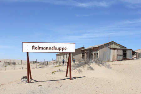 Kolmannskuppe, Namibia, October 2016 Tourists walk along vintage grungy buildings and a signboard or Kulmannskoppe in the ghost town in the desert. This was a former diamond mining town.