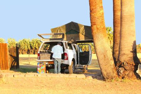 Kalahari desert, Namibia, October 2016 Seniors with a camping tent on the roof at a campsite Editorial