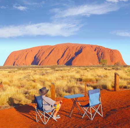 Uluru, Australia, December 2015 Man in a camping chair enjoys the colorful sunset of Uluru Ayers Rock