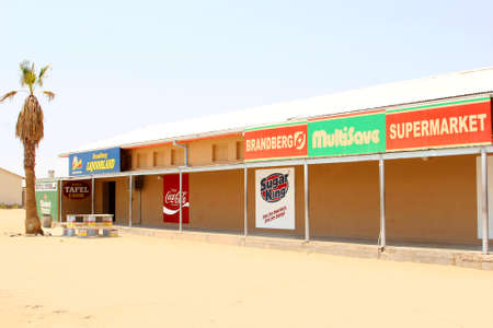 coke bottle: Uis, Namibia, Africa, October 2016 Small shopping mall with advertisement signs of a supermarket, coke, bottle store, liquor shops and Sugar King