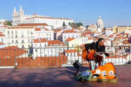 Lisbon, Portugal, January 2017 Street musician plays guitar at a viewpoint over the old town of Lisbon