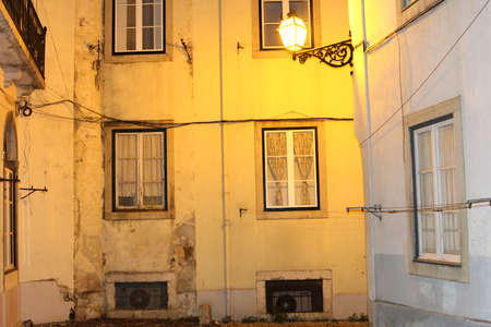 Facades of old houses and an old lantern at night in Alfama, Lisbon, Portugal Stock Photo