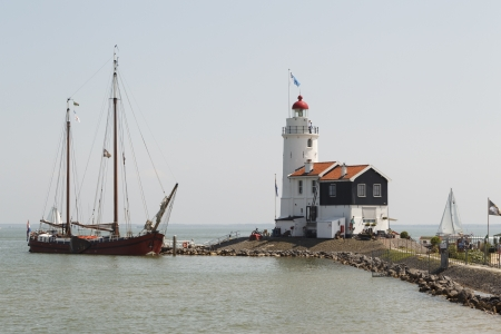 marken: An old wooden sailboat visits the Paard of Marken lighthouse in Marken, the Netherlands.