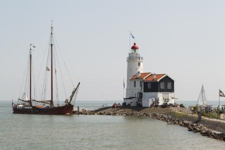 """Een oude houten zeilboot bezoekt het """"Paard van Marken"""" vuurtoren in Marken, Nederland."""
