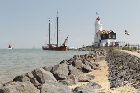 """Een oude houten zeilboot bezoekt het 'Paard van Marken """"vuurtoren in Marken, Nederland. Redactioneel"""