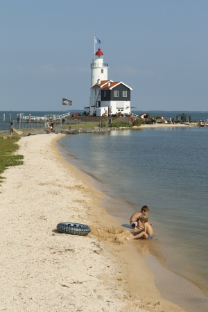 People are sunbathing and playing in the water at the Paard van Marken lighthouse in Marken, the Netherlands.