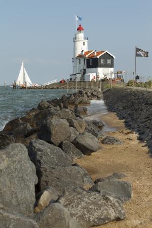 A sailboat sails past the Paard of Marken lighthouse in Marken, the Netherlands. Redakční