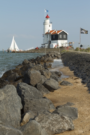 A sailboat sails past the Paard of Marken lighthouse in Marken, the Netherlands. Editorial
