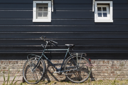 Typically Dutch image of a bike  with a flat tire  parked against a wooden house