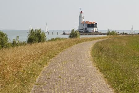 Landscape photo showing a dyke leading up to a beautiful old lighthouse  Reklamní fotografie