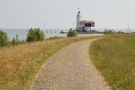 Landschap foto toont een dijk in de aanloop naar een mooie oude vuurtoren